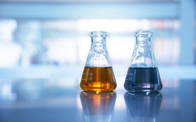 two glass flasks with orange and black solution in chemical science laboratory background